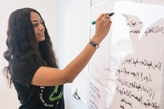 Female writing code on whiteboard